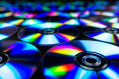 CDs / DVDs lying on a black background with reflections of light. royalty free stock photos