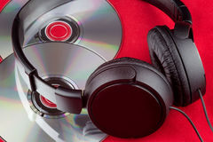 CDs and Headphones on a Red Background. Compact discs and headphones on a red cloth surface Royalty Free Stock Photos