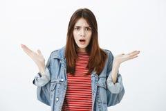 Ce qui vous veulent de moi Portrait alimentée d'amie mignonne fâchée dans la veste de denim, les paumes augmentées de propagation Photo libre de droits