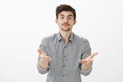 Ce qui vous veulent de moi Portrait de type barbu beau fatigué contrarié dans la chemise rayée, tirant des mains vers l'appareil- Images stock
