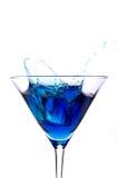 Ce splashing into a blue martini Stock Image