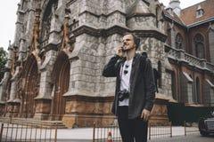 Ce touriste se tient sur la route près du vieux bâtiment brun Il parle au téléphone et sourit avec un gai photographie stock