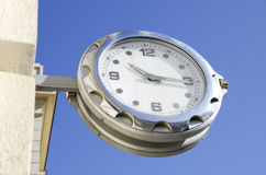 Ceas agatat. Watch hanging from a building on a blue background Stock Images