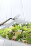 Ceasar salad. On white plate and antique folk, on white wooden background Stock Image