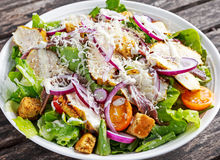 Ceasar salad with grilled chicken fillets, red onion rings, lettuce, orange cherry tomatoes, croutons, grated parmesan Stock Image