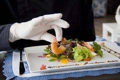 Ceasar salad with shrimps on a plate and hand of kitchener Stock Photo