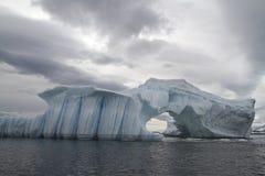 Ceberg με την αψίδα και gullies σε ένα νεφελώδες φθινόπωρο Στοκ Φωτογραφίες