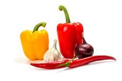 Cebola, alho, pimentas de pimentão e pimenta de sino vermelha, amarela e verde no fundo branco Fotos de Stock Royalty Free