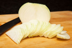 Cebola branca cortada na placa de corte Foto de Stock
