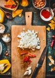 Cebola, pimentão e alho desbastados na placa de corte de madeira com faca Culinária mexicana picante no fundo rústico da mesa de  Imagem de Stock Royalty Free
