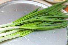 Cebola verde fresca na mesa de cozinha, close-up imagens de stock royalty free