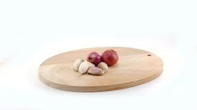 Cebola vermelha e alho na placa de corte de madeira Imagens de Stock Royalty Free