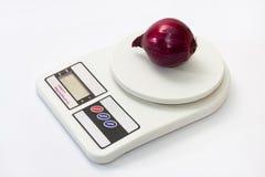 Cebola vermelha em uma escala branca digital da cozinha Imagens de Stock