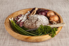 Cebolas, bandeja de madeira do pão de mistura com salsa e sal, aipo do salame, faca Fotografia de Stock Royalty Free