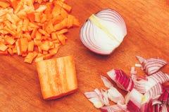 Cebolas e cenouras cortadas na placa de desbastamento Fotos de Stock Royalty Free