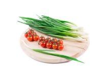 Cebolas e tomates de cereja em uma placa de madeira Imagem de Stock Royalty Free