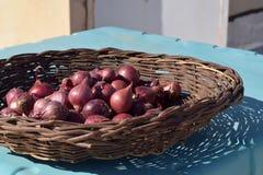 Cebolas em uma cesta de madeira imagens de stock royalty free