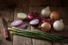 Cebolas frescas da exploração agrícola sortido em uma tabela de madeira com cebolas da mola Imagem de Stock