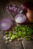 Cebolas frescas da exploração agrícola sortido em uma tabela de madeira com cebolas da mola Imagens de Stock