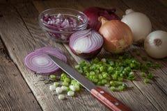 Cebolas frescas da exploração agrícola sortido em uma tabela de madeira com cebolas da mola Imagens de Stock Royalty Free