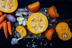 Cebolas frescas dos vegetais da abóbora e do outono, cenouras, alho, gengibre na placa de madeira Modo do outono fotos de stock