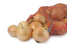 Cebolas que caem fora de um saco isolado no branco Fotografia de Stock Royalty Free