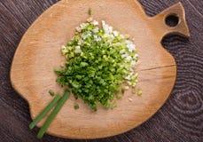 Cebolas verdes cortadas na placa de corte Imagem de Stock
