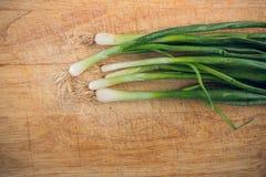 Cebolas verdes frescas que encontram-se em uma placa de desbastamento de madeira A vista da parte superior imagem de stock royalty free