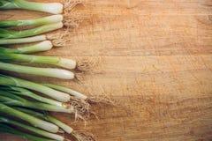 Cebolas verdes frescas que encontram-se em uma placa de desbastamento de madeira A vista da parte superior fotos de stock