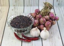 Cebolas vermelhas com alho orgânico inteiro e o Riceberryon tailandês de madeira Fotografia de Stock Royalty Free