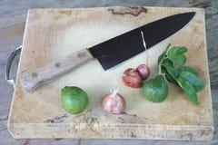 Cebolla, bergamota, cuchillo de cocina y bloque en la tabla de madera Imagen de archivo