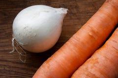 Cebolla blanca y dos zanahorias Imagen de archivo libre de regalías