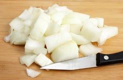 Cebolla cortada en cuadritos con un cuchillo de cocina Imagen de archivo libre de regalías
