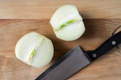 Cebolla cortada en dos en fondo de madera Fotografía de archivo