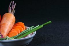 Cebolla del tomate, de la zanahoria y del resorte en un plato Foto de archivo libre de regalías