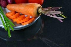 Cebolla del tomate, de la zanahoria y del resorte en un plato Fotos de archivo libres de regalías