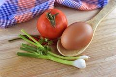 Cebolla, huevo, chile y tomate en fondo de madera Fotos de archivo