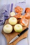 Cebollas blancas grandes peladas con el cuchillo de cocina en un tablero de madera Imagen de archivo