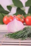 Cebollas con hinojo contra un tomate Imagenes de archivo