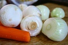 Cebollas de la zanahoria y setas peladas del champiñón en un tablero de madera en la cocina Productos vegetales para la sopa Imagen de archivo libre de regalías