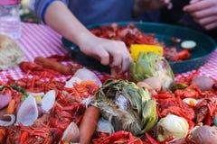 Cebollas de los cangrejos de la salchicha de la alcachofa y llenado más en la tabla en la ebullición de los cangrejos con las man foto de archivo libre de regalías