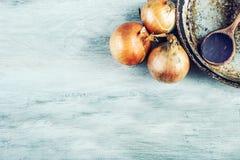 Cebollas de madera de la cuchara tres de la cacerola vieja de la cocina en la tabla de madera Fotos de archivo libres de regalías