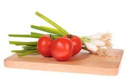 Cebollas del resorte con los tomates fotografía de archivo libre de regalías