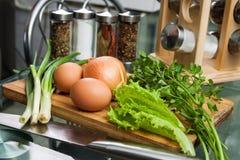 Cebollas e hierbas de los huevos en una tabla de cocina Fotos de archivo