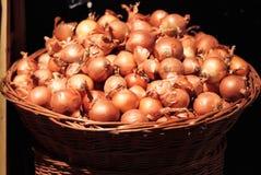 Cebollas en cesta de mimbre grande imagen de archivo