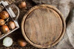 Cebollas en cesta Tabla de cortar de madera, visión superior Fondo de madera rústico Fotos de archivo libres de regalías