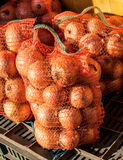Cebollas en sacos de la malla en el mercado imagenes de archivo