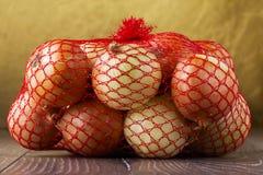 Cebollas en un bolso Imagenes de archivo