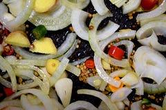 Cebollas mezcladas, jengibre, pimienta, semillas, raíz de cúrcuma en una cacerola fotografía de archivo libre de regalías