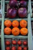 Cebollas, naranjas y tomates en una tabla Foto de archivo libre de regalías